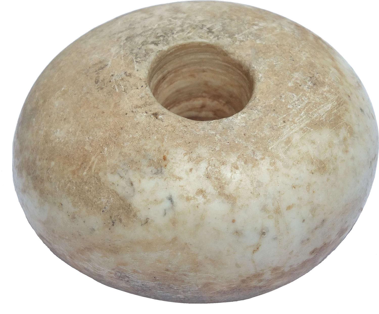 An Egyptian marble doughnut-shaped macehead, c. 4000-3000 B.C.
