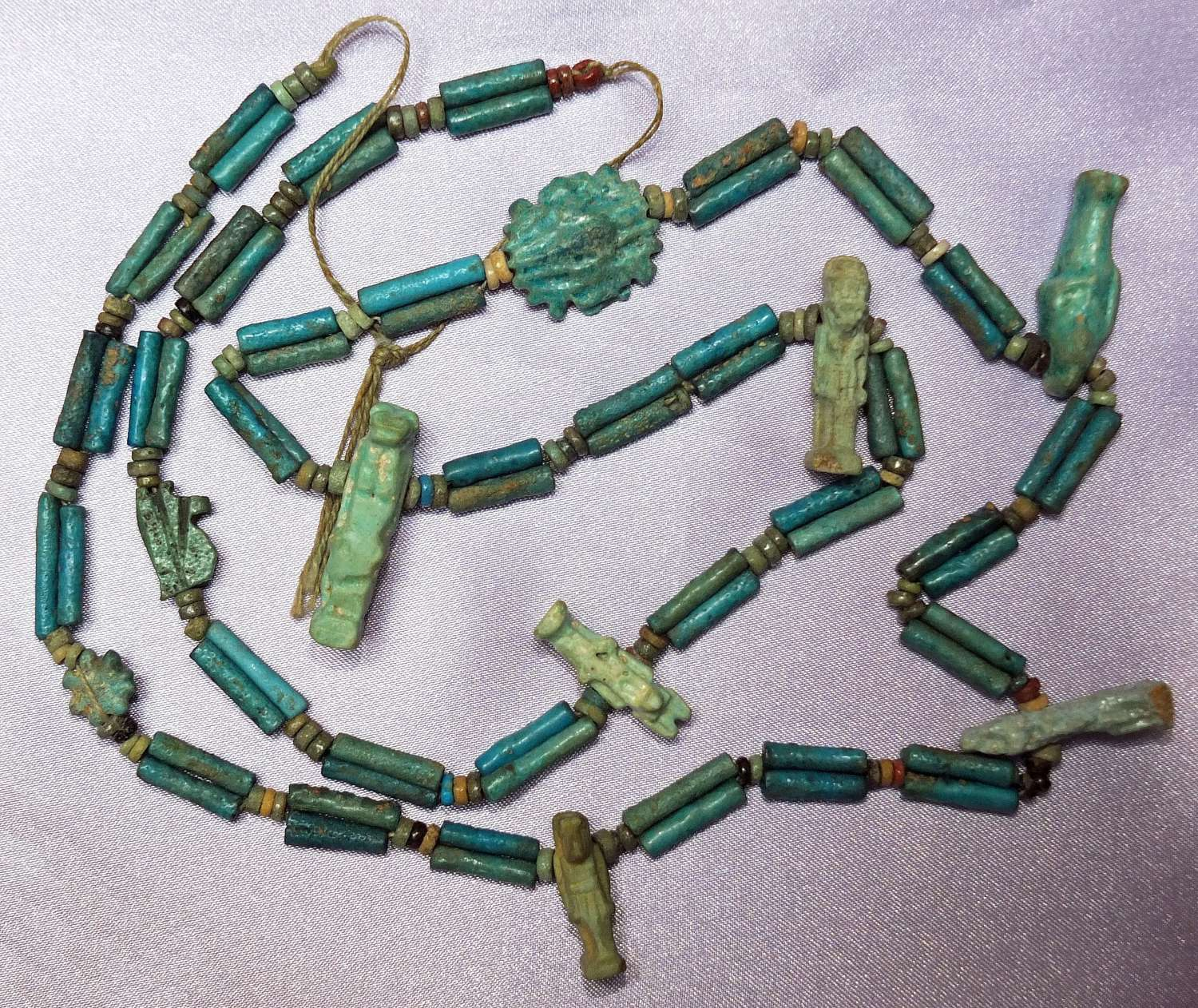 An Egyptian restrung amuletic blue faience bead necklace