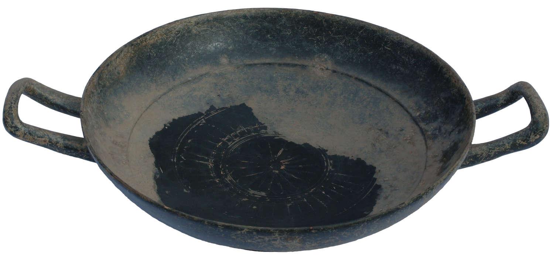 A Greek black glazed stemless kylix, 4th Century B.C.