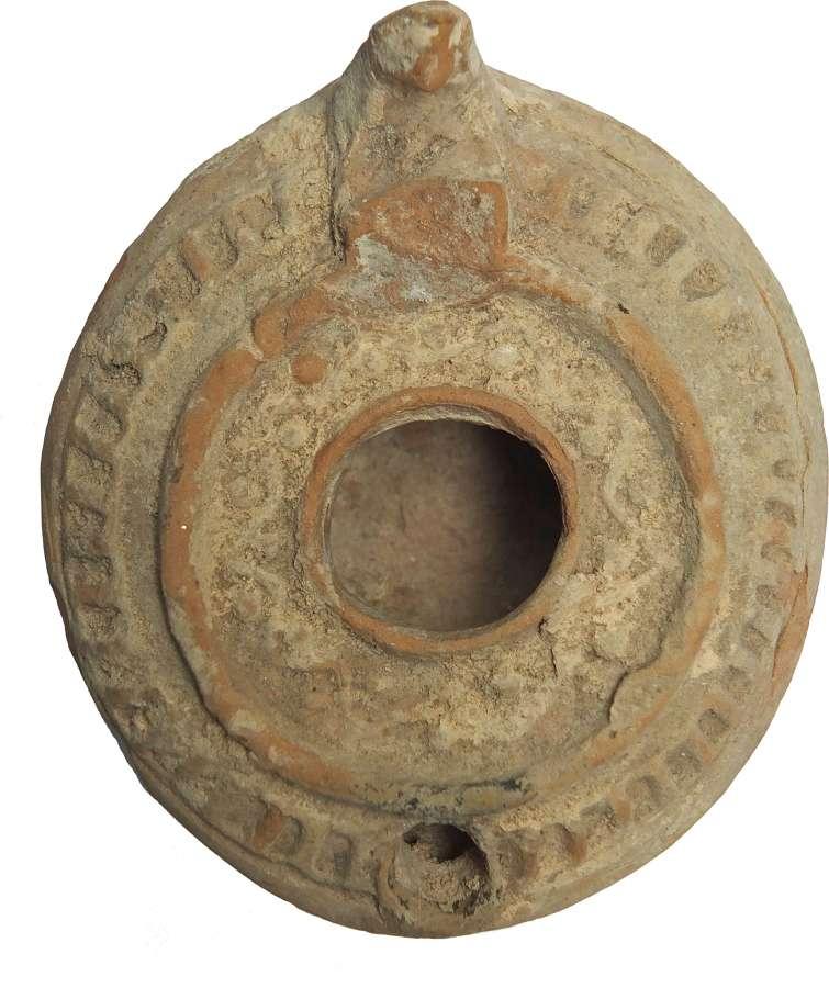 A fawn circular terracotta oil lamp, c. 600-800 A.D.