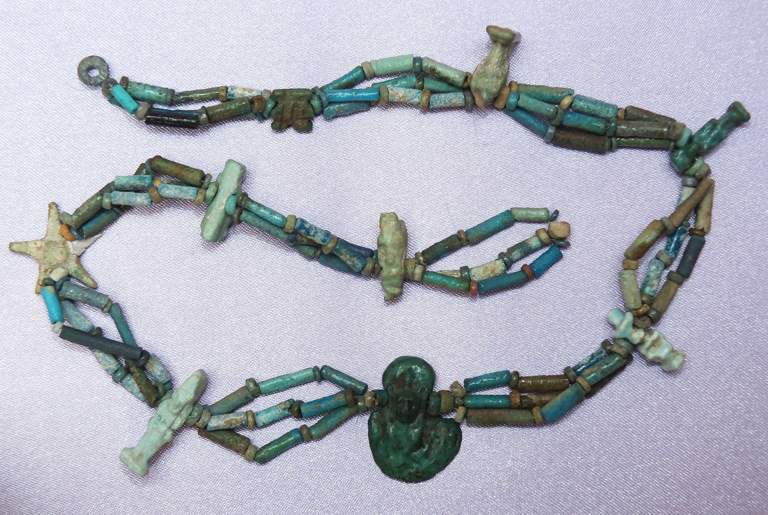 A triple-stranded necklace of Egyptian faience beads with nine amulets