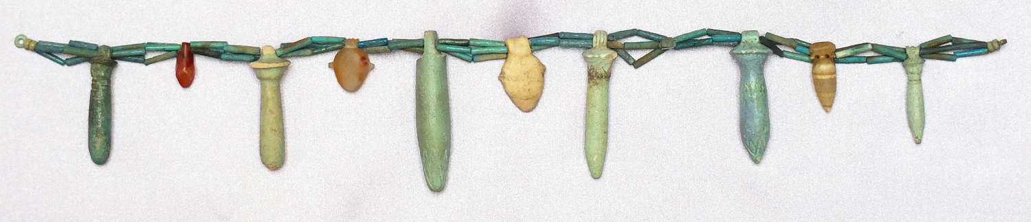 A triple-stranded necklace of Egyptian faience beads with ten amulets
